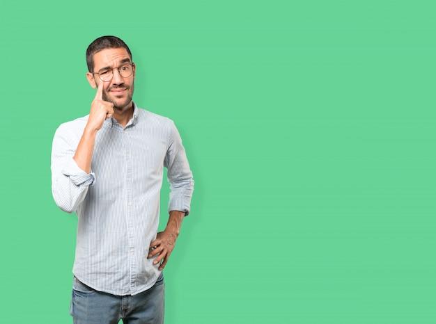 Aarzelende jonge man die een gebaar maakt om voorzichtig te zijn met zijn hand die naar zijn oog wijst