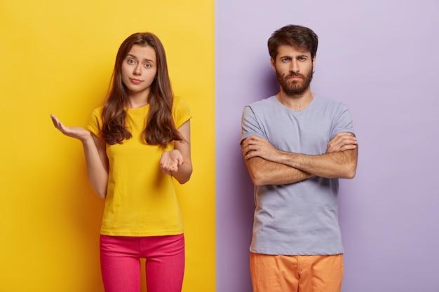 Aarzelende jonge vrouw spreidt handen met twijfel, draagt vrijetijdskleding, ontevreden man houdt handen gekruist, ontevredenheid met iets