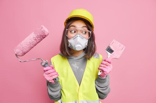 Aarzelende jonge vrouwenbouwer draagt een technisch uniform beschermend masker en helm houdt bouwapparatuur op de bouwplaats vast