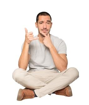 Aarzelende jongeman die een gebaar maakt van bellen met de hand