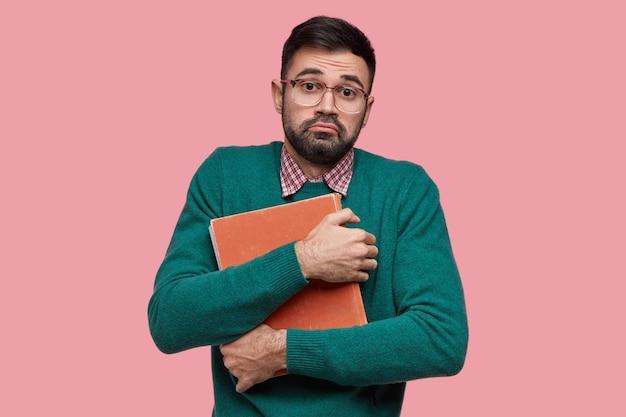 Aarzelende knappe ongeschoren man heeft dikke baard, draagt een oude encyclopedie bij zich, wil nieuwe informatie over een bepaald onderwerp leren