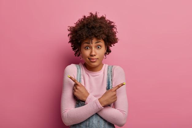 Aarzelende, onwetende vrouw met afrohaar denkt wat te bestellen, kruist armen over het lichaam en wijst zijwaarts, draagt coltrui, heeft verbaasde blik, probeert een keuze te maken, toont twee varianten