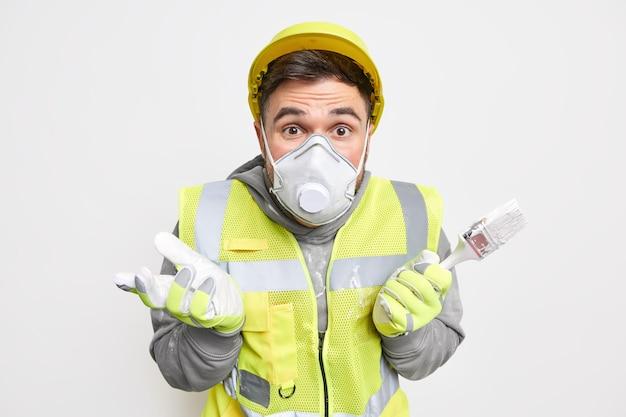 Aarzelende reparateur spreidt handen draagt constructie-uniform beschermend gezichtsmasker en handschoenen houdt kwast vast voor het opknappen van huis