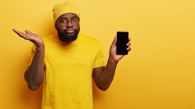 Aarzelende verwarde man kiest nieuwe slimme telefoon, houdt modern elektronisch apparaat vast met mock-up scherm, steekt twijfelachtig handpalm op, aarzelt om te kopen, draagt heldere modieuze gele hoed en t-shirt