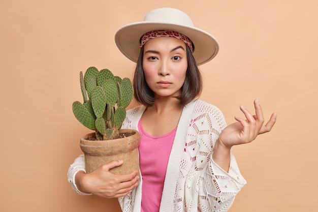 Aarzelende vrouw weet niet hoe ze om cactus moet geven, lijkt geen idee
