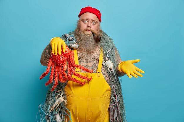 Aarzelende zeeman haalt schouders op, houdt octopus in de hand, draagt rubberen handschoenen, heeft zee-avontuur, rookt pijp, bezig met vissen