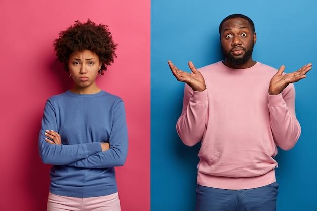 Aarzelende zwarte man spreidt zijn handpalmen van aarzeling, weet niet hoe hij vriendin moet kalmeren die beledigd staat met gevouwen armen