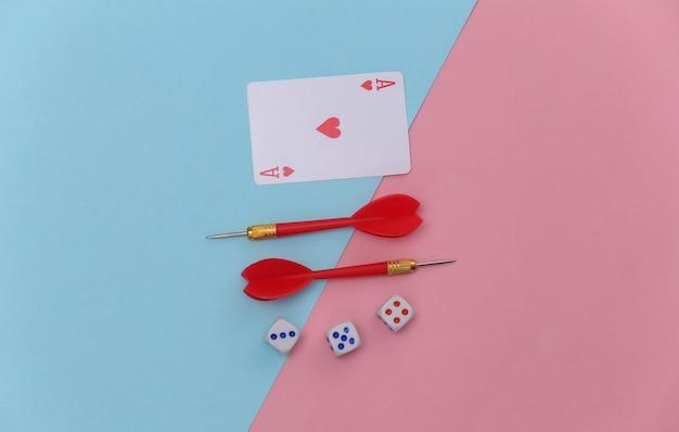 Aas van harten, dobbelstenen en darts op roze blauwe pastel achtergrond. bovenaanzicht