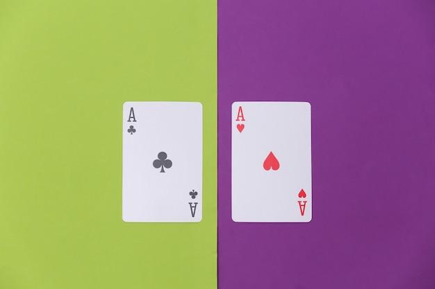 Aas van harten en clubs op een groen-paarse achtergrond. bovenaanzicht