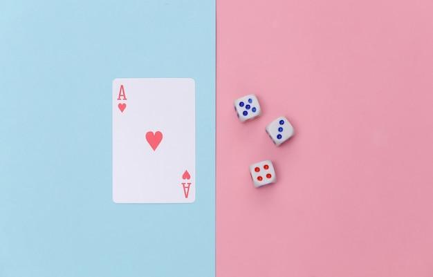 Aas van harten en dobbelstenen op roze blauwe pastel achtergrond. bovenaanzicht