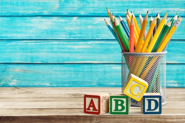 Abc-blokken en potloden op bureauachtergrond