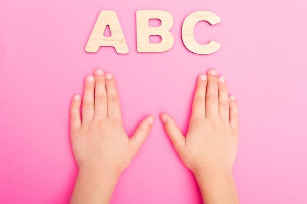 Abc-brieven in de handen van het kind op roze achtergrond