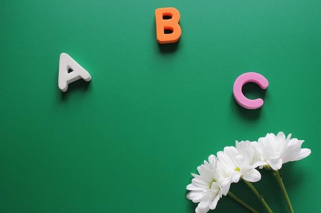 Abc - de eerste letters van het engelse alfabet en drie witte chrysanten