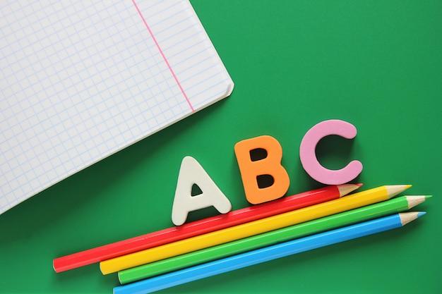 Abc - de eerste letters van het engelse alfabet. schoolnotitieblok en kleurpotloden