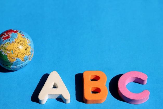 Abc eerste letter van het engelse alfabet en kleine wereldbol op blauw