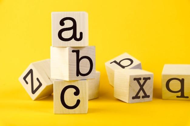 Abc geschreven op houten kubussen met gele achtergrond