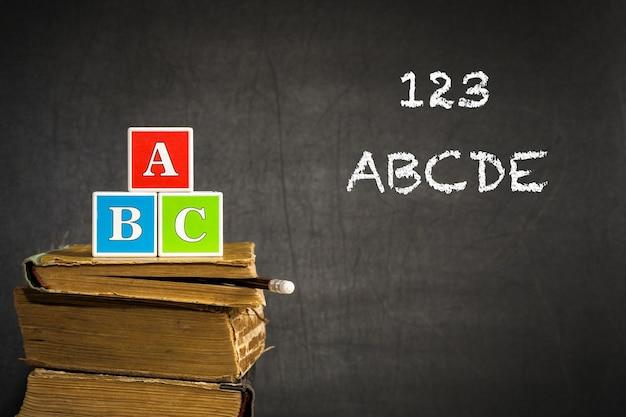 Abc op oude boeken in de klas tegen bord. schoolconcept