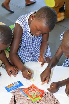 Abidjan / ivoorkust - 1 december 2015: een 8-jarig schoolmeisje uit ivoirien tekenen op wit papier.