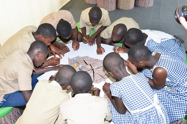 Abidjan / ivoorkust - 1 december 2015: een 8-jarige ivoirien schoolkinderen tekenen op wit papier.