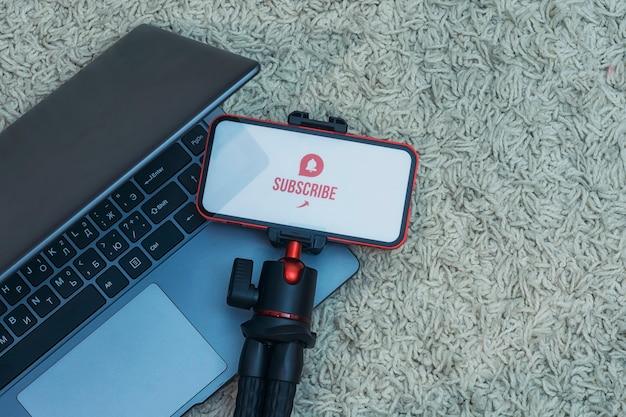 Abonneer je op het internetkanaal op het smartphonescherm op een flexibel statief met laptop tegen de achtergrond van het tapijt.