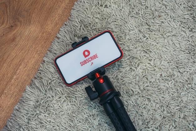 Abonneer je op het internetkanaal op het smartphonescherm op een flexibel statief tegen de achtergrond van het tapijt.
