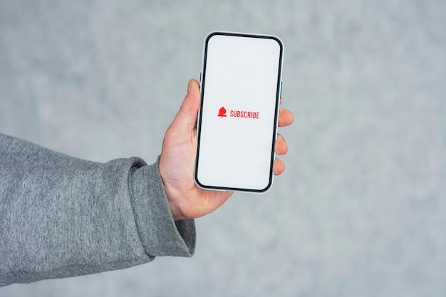 Abonneer u op het internetkanaal op het scherm van de smartphone. man houdt smartphone close-up met pictogram.