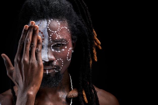Aborigen man met etnische make-up sluitende helft van gezicht, portret in studio op zwarte muur. diversiteit, nationaliteit, etniciteit, indisch, inboorling