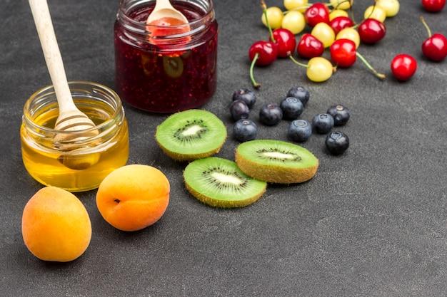 Abrikoos en kers, kiwi, honing en jam op zwarte achtergrond