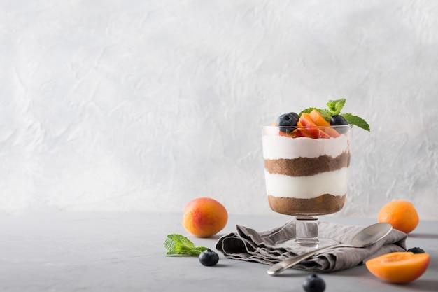 Abrikoos kleinigheid, chocoladekoekje, gelaagd dessert met bessen en roomkaas op grijs.