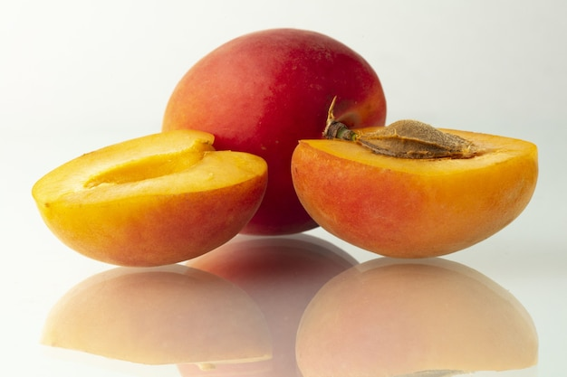 Abrikoosvruchten en de helft geïsoleerd op witte achtergrond