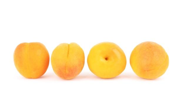 Abrikoosvruchten met bladeren die op witte achtergrond worden geïsoleerd