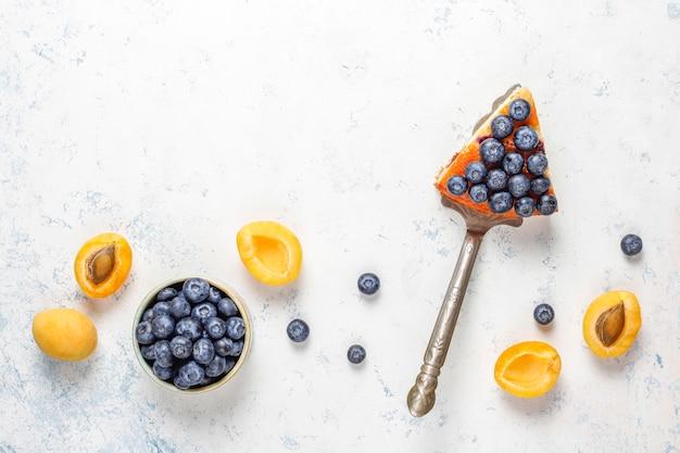 Abrikozen- en bosbessencake met verse bosbessen en abrikozenvruchten