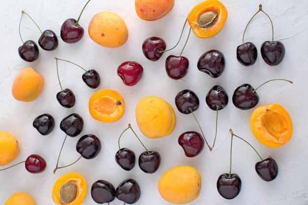 Abrikozen en kersen op wit worden geïsoleerd zomerfruit en bessen oogsten