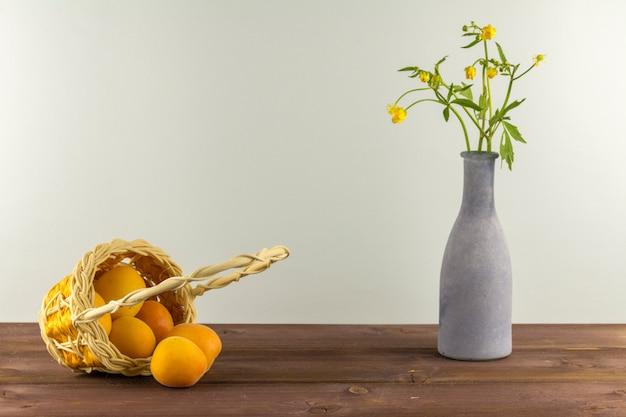 Abrikozen in de mand. vaas met wilde bloemen op een blauwe achtergrond. zomerstemming