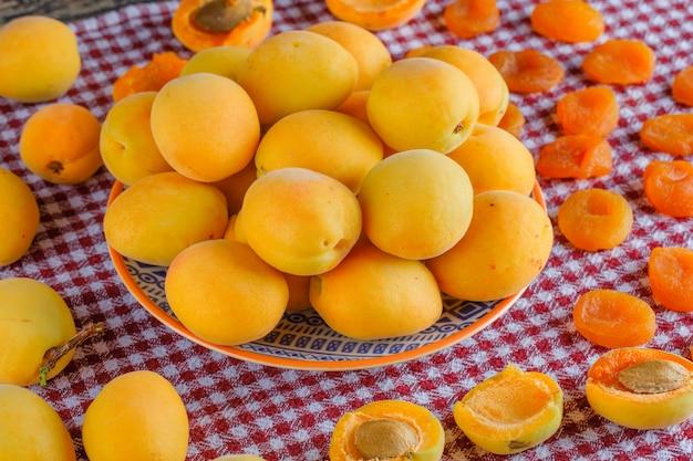 Abrikozen in een plaat met gedroogde abrikozen bovenaanzicht op een picknick doek