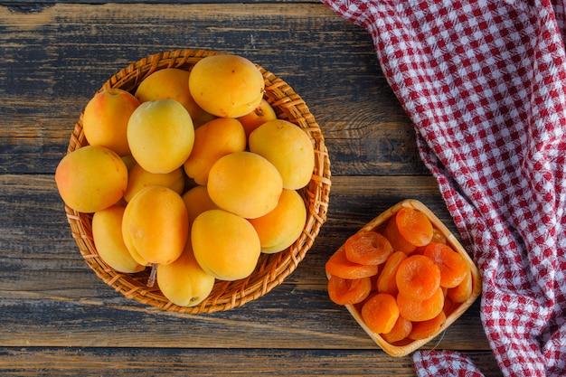 Abrikozen in een rieten mand met gedroogde abrikozen plat lag op picknick doek en houten tafel
