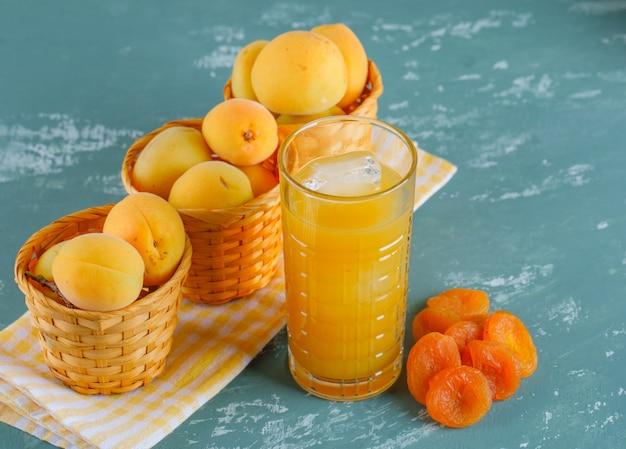 Abrikozen in manden met gedroogde abrikozen, sap bovenaanzicht op gips en picknick doek