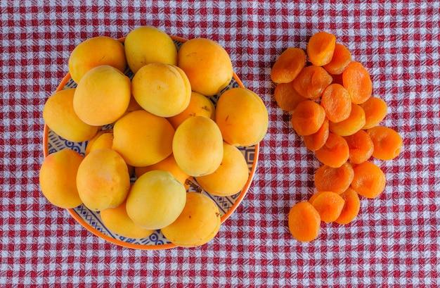 Abrikozen met gedroogde abrikozen in een plaat op picknick doek, plat lag.