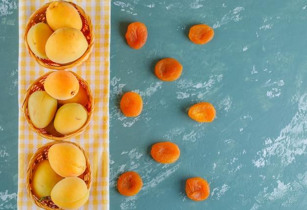 Abrikozen met gedroogde abrikozen in manden op gips en picknick doek, bovenaanzicht.