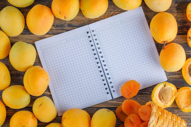 Abrikozen met gedroogde abrikozen, opende notitieblok op houten tafel, plat lag.