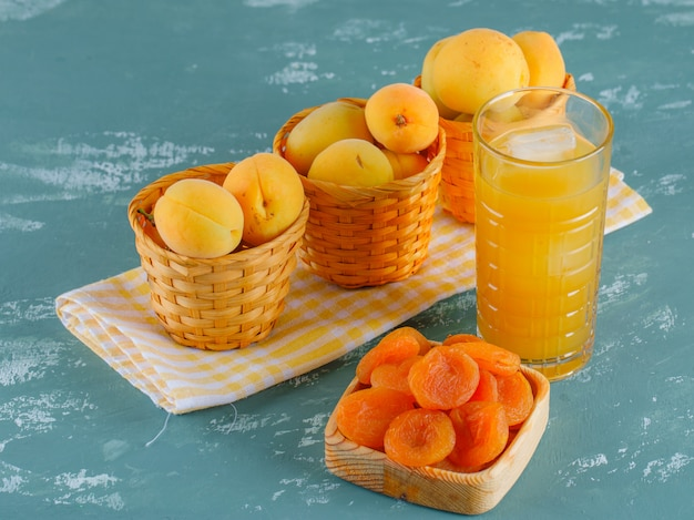 Abrikozen met gedroogde abrikozen, sap in manden op gips en picknick doek, bovenaanzicht.