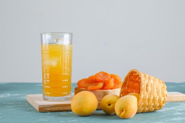 Abrikozen met gedroogde abrikozen, snijplank, sap in een mand, zijaanzicht.
