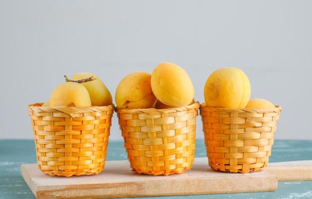 Abrikozen met snijplank in manden