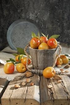 Abrikozen of nectarines in een oude houten emmer