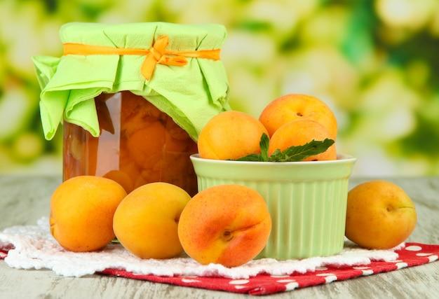 Abrikozenjam in glazen pot en verse abrikozen, op houten tafel