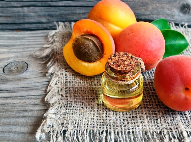 Abrikozenolie van abrikozenpitten in een glazen pot en verse rijpe abrikozen op oude houten tafel