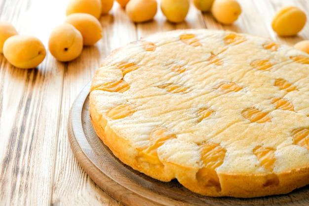 Abrikozenperziktaart met abrikozenvruchten op de achtergrond eenvoudig recept voor zomercake voor theetijd