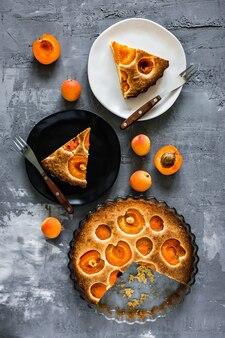 Abrikozentaart, een wit en een zwart bord met stukjes van een taart en vorken, abrikozen rond