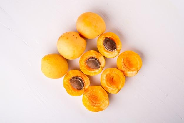 Abrikozenvruchten die op witte oppervlakte worden gesneden