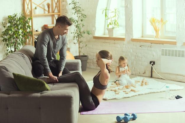 Abs trainen met man. jonge vrouw die fitness, aerobics, yoga thuis, sportieve levensstijl en thuisgymnastiek uitoefent.